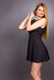 Portrait of happy young blonde woman wearing a mini black dress Stock Photo