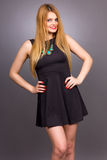 Portrait of happy young blonde woman wearing a mini black dress Royalty Free Stock Photos