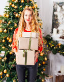 Portrait of happy young blondy woman with many christmas present. Box, at a Christmas decorations Royalty Free Stock Photo