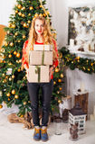 Portrait of happy young blondy woman with many christmas present. Box, at a Christmas decorations Royalty Free Stock Photos