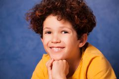 Portrait of happy young boy with curly hair. Against blue background Royalty Free Stock Photo