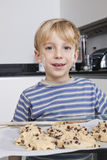 Portrait of happy young boy in front of baking tray of cookies Royalty Free Stock Image