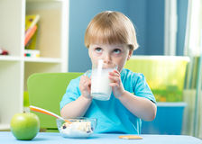 Portrait of happy young boy holding glass with milk stock photos