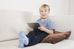 Portrait of happy young boy holding tablet PC on sofa Royalty Free Stock Image