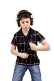 Portrait of a happy young boy listening to music and dancing. Portrait of a happy young boy listening to music on headphones and dancing against white background Royalty Free Stock Images