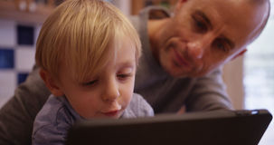 Portrait of a happy young boy reading an e-book with his father Stock Photography