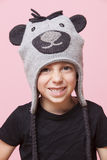 Portrait of a happy young boy wearing monkey cap over pink background Royalty Free Stock Images