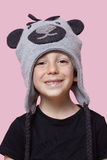 Portrait of a happy young boy wearing monkey cap over pink background Stock Photos