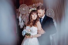 Portrait of happy young bride and groom in a classic interior near the dream catchers. Wedding day, love theme. First day of a new stock images