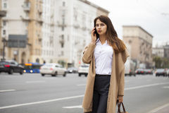 Portrait of happy young brunette woman in beige coat talking on Royalty Free Stock Images