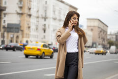 Portrait of happy young brunette woman in beige coat talking on Stock Images