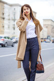 Portrait of happy young brunette woman in beige coat talking on Stock Photography