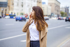 Portrait of happy young brunette woman in beige coat talking on Royalty Free Stock Photos