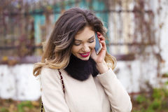 Portrait of happy young brunette woman in beige coat talking on Royalty Free Stock Image
