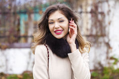 Portrait of happy young brunette woman in beige coat talking on Stock Image