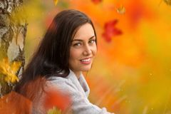 Portrait of young woman with falling autumn leaves. Stock Photos