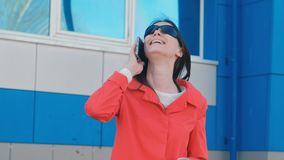 Portrait of happy young brunette woman in sunglasses speaks on the phone the beside blue building. stock footage