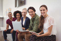Portrait of happy young business colleagues working together by wall at office Royalty Free Stock Photography