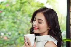 Portrait of happy young business woman with mug in hands drinking coffee stock image