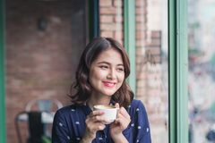 Portrait of happy young business woman with mug in hands drinkin Stock Photo