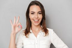 Portrait of a happy young business woman showing ok. Gesture isolated over white background Stock Photography