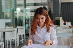 Portrait of happy young business woman sitting and holding paperwork or charts in her hands against smile his work in office. Portrait of happy young business Royalty Free Stock Photos