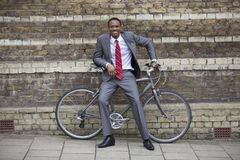 Portrait of a happy young businessman with bicycle against brick wall Royalty Free Stock Photo