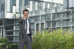 Portrait of happy young businessman pointing at you outside office building Royalty Free Stock Photo