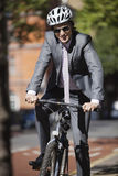 Portrait of happy young businessman riding bicycle Stock Images