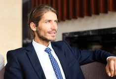 Portrait of happy young businessman sitting on sofa in hotel lobby. Royalty Free Stock Photography