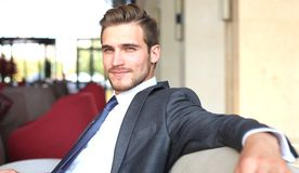 Portrait of happy young businessman sitting on sofa in hotel lobby. Stock Photography