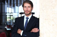 Portrait of happy young businessman standing in hotel lobby. Royalty Free Stock Images