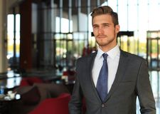 Portrait of happy young businessman standing in hotel lobby. Stock Photos