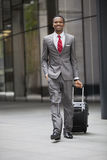 Portrait of happy young businessman walking with wheeled suitcase Royalty Free Stock Photo