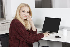 Portrait of happy young businesswoman with laptop sitting at desk in office Stock Photography