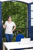 Portrait of happy young businesswoman standing by balcony with laptop on desk Royalty Free Stock Images