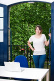 Portrait of happy young businesswoman standing by balcony with laptop on desk Stock Photo