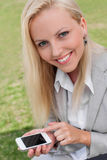 Portrait of happy young businesswoman using smart phone in lawn Royalty Free Stock Photo