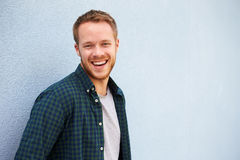 Portrait of happy young Caucasian man against grey wall Stock Image