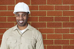 Portrait of happy young construction worker with hardhat over brick wall Stock Photography