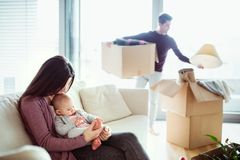 A portrait of young couple with a baby and cardboard boxes moving in a new home. A portrait of happy young couple with a baby and cardboard boxes, moving in a stock photography