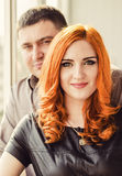 Portrait of happy young couple. Portrait of beautiful women with red hair and men in the background Stock Image