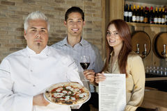 Portrait of happy young couple with chef holding pizza Royalty Free Stock Images