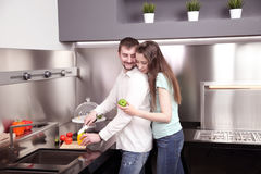 Portrait of happy young couple cooking together in the kitchen. Stock Image