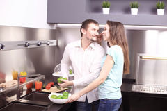 Portrait of happy young couple cooking together in the kitchen. Royalty Free Stock Images