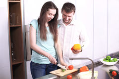 Portrait of happy young couple cooking together in the kitchen. Royalty Free Stock Photography