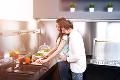 Portrait of happy young couple cooking together in the kitchen Stock Image