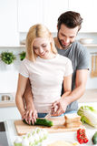 Portrait of happy young couple cooking together in the kitchen Stock Photo