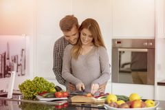 Portrait of happy young couple cooking together in the kitchen at home. royalty free stock photos