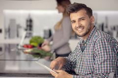 Portrait of happy young couple cooking together in the kitchen at home. stock image